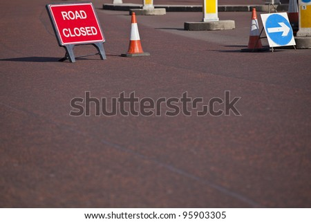 Signs informing about a closed road with arrow for diversion sign - stock photo