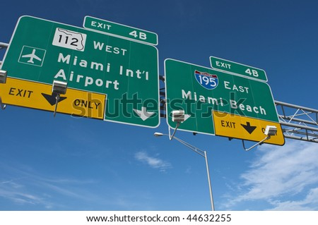 Signs marking the way to The Miami International Airport and Miami Beach - stock photo