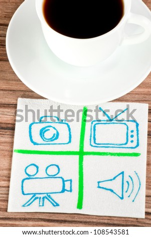 Signs of TV and photo on a napkin and cup of coffee - stock photo