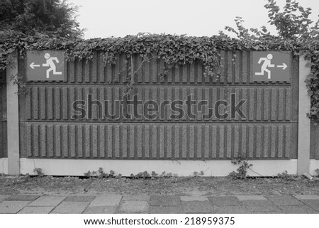 Signs on a train station platform as metaphor for the many choices a human has to make during the journey called life (black and white version) - stock photo