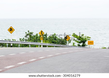 Signs on curves and slopes road beside the sea - stock photo