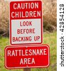 Signs warning about children at play and rattlesnakes in the area - stock photo