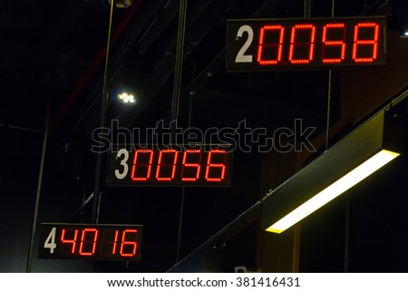 Signs with numbers indicating the order in the queue hanging on the ceiling offices. Digital indicators order.  - stock photo