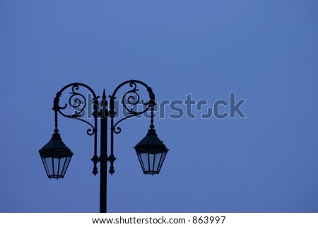 Sihouette of Old Street Light Against Blue Sky - stock photo