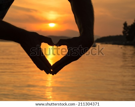 Siilhouette of hands in heart shape at sunset