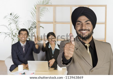 Sikh business executives showing thumbs up sign - stock photo