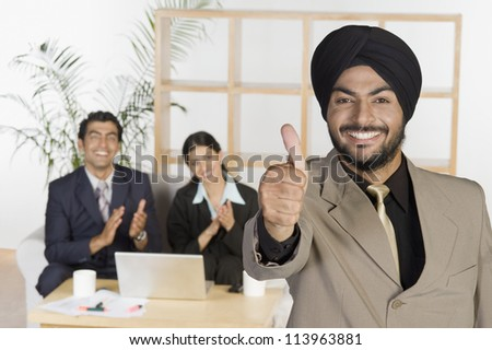 Sikh businessman showing thumbs up sign - stock photo