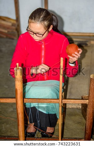 SIKKIM, INDIA - MAR 13, 2017: Unidentified Indian young black-haired girl sits and holds a ball of threads in her hand.
