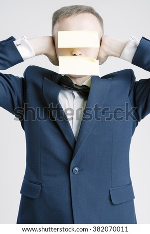 Silence and Secrets Concepts And Ideas. Portrait of Caucasian Businessman With Paper Sticker on Forehead and Mouth. Hands Closing Ears.Vertical Image - stock photo