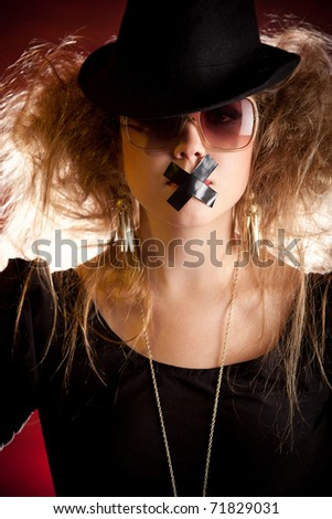 Silenced eccentric woman with tape over her mouth - stock photo