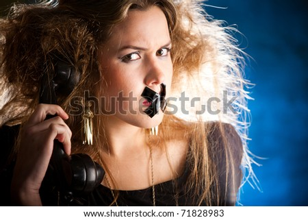 Silenced woman with tape over her mouth holding the phone - stock photo