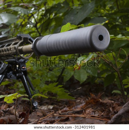 Silencer on a rifle that is in a bunch of trees - stock photo
