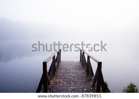 Silent  docks in the morning fog on the lake - stock photo