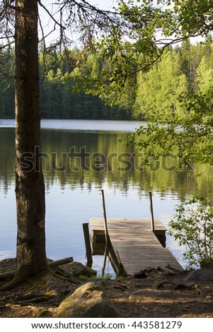Silent evening by the lake. An image of an empty pier on a small lake in Finland. Image taken during sunset. Forest is reflected from the still water. Focus point is on the pier. - stock photo