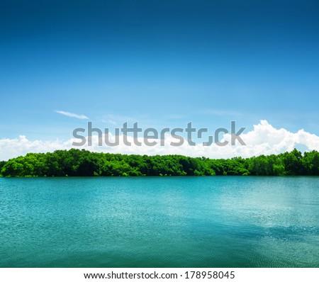 Silent lake under blue sky. - stock photo