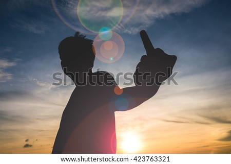 silhouaette with human Hand Gesturing With Middle Finger - stock photo