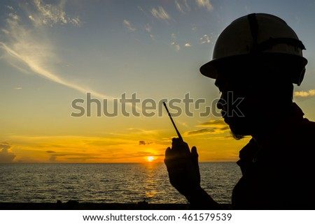 Silhouete of offshore crew holding walkie talkie isolated with sunrise view