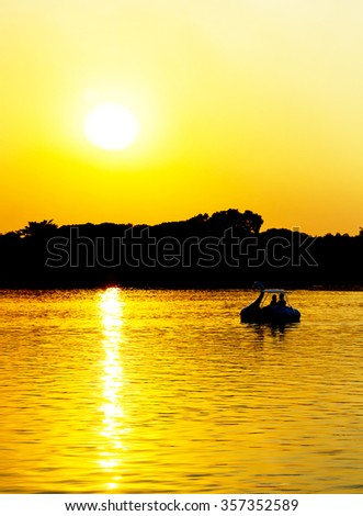 Silhouette a couple on swan boat in the lake, love and romantic concept - stock photo