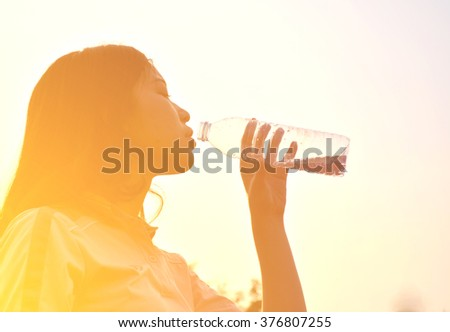 Silhouette a girl drinks water after sport and soft focus - stock photo