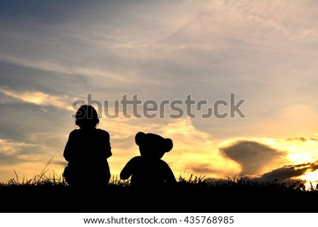 Silhouette a girl  with teddy bear on mountain and sky sunset