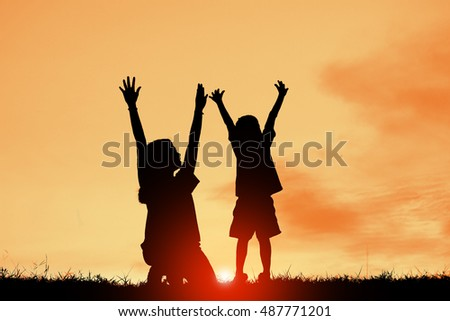 Silhouette a Mother her son at the sunset and hands up. Concept of friendly family.