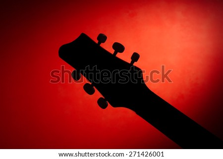 Silhouette Acoustic Guitar Fretboard in Black on a red background - stock photo