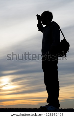 Silhouette against a sunset sky of a man standing wearing a backpack scanning the horizon with his hand raised to his eyes - stock photo
