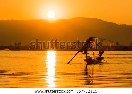 Silhouette against the morning light fishing Inle Lake, Myanmar. - stock photo