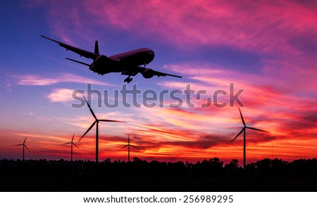 silhouette air plane flying on wind turbine farm at dusk - stock photo