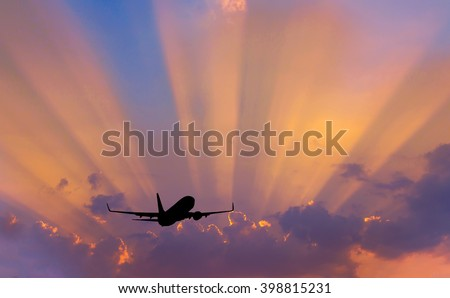 Silhouette airplane flying on sunbeams background. - stock photo