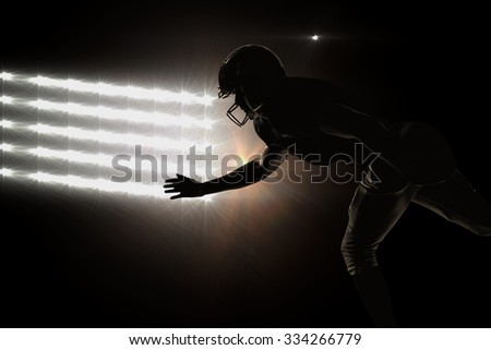 Silhouette American football player jumping against spotlights