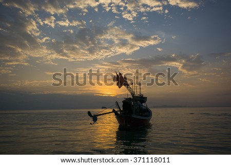 SILHOUETTE  ANCHORED FISHERMAN-LONG TAIL BOAT AT THE SEA , TWILIGHT SKY CLOUDS BACKGROUND
