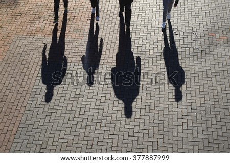 Silhouette and shadows of people walk on a pavement made of bricks - stock photo
