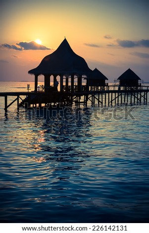 Silhouette    arbor over water for rest at sunset.,with a retro effect    - stock photo