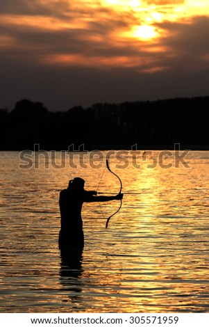 Silhouette archery shoots a bow at a target in sunset sky and cloud