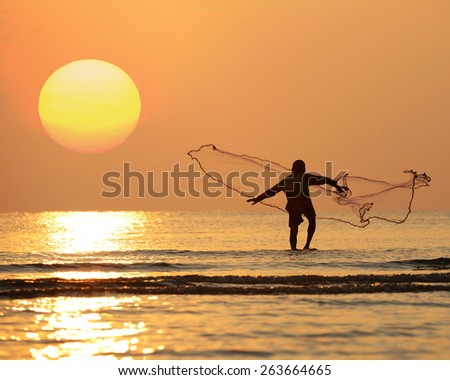 Silhouette asian fisherman throwing net in the sea at morning with big yellow sun. Hua Hin, Thailand - stock photo