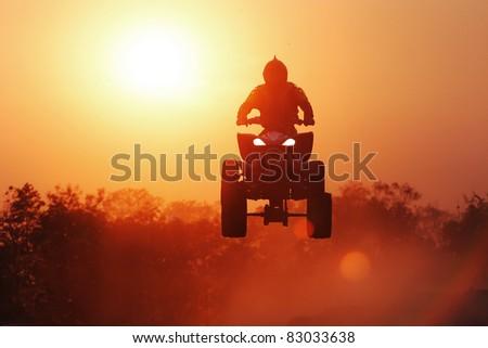Silhouette ATV jump - stock photo