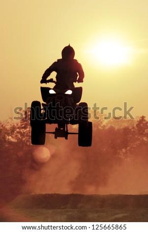 Silhouette ATV jump on dirt tract - stock photo