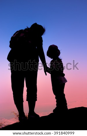 Silhouette back view of mother and child hikers enjoying the view at the top of a mountain. Colorful sunset sky background. Friendly family. - stock photo