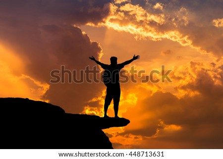 silhouette backpacker man standing raised up arms achievements successful and celebrate success on top of the mountain in sunset.