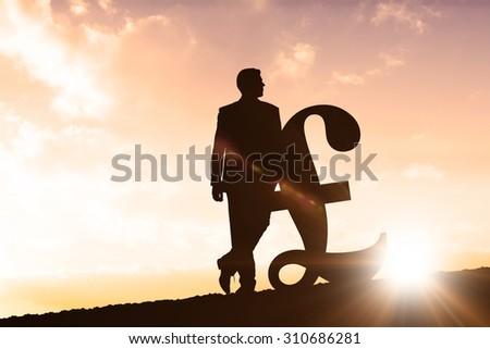 Silhouette beside pound symbol against sun shining - stock photo