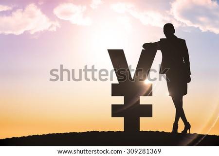Silhouette beside yen symbol against sun shining - stock photo
