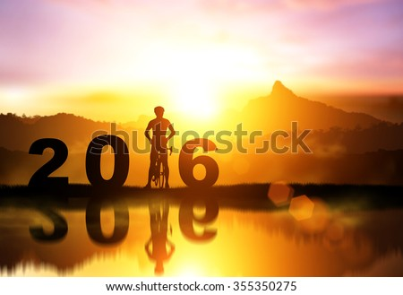 Silhouette bicycle in 2016 text on sunset,Friendship in bicycle sport.happy new year - stock photo