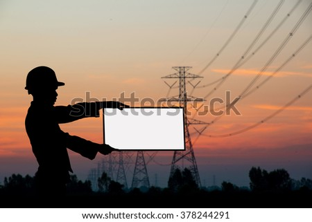 silhouette black man survey and civil engineer  casual man holding white sign to write it on your text over Blurred construction worker on construction site. examination, inspection, survey - stock photo