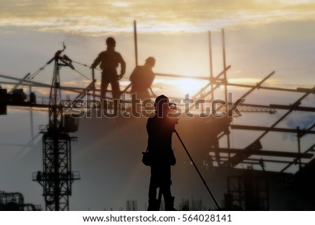 silhouette black man survey and civil engineer stand on ground working in a land building site over construction worker on construction site. examination, inspection, survey .