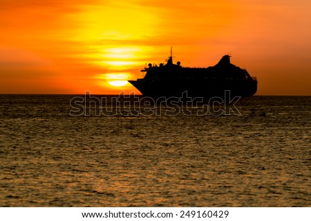 silhouette boat at sunset - stock photo