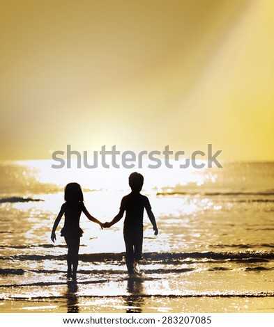 Silhouette boy and girl on the sea against the strong sunrise