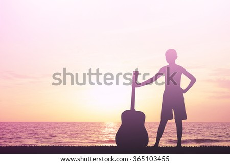 Silhouette boy holding a guitar. - stock photo
