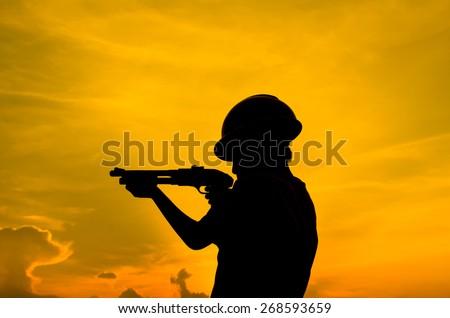 Silhouette boy holding shotgun with sun set. - stock photo