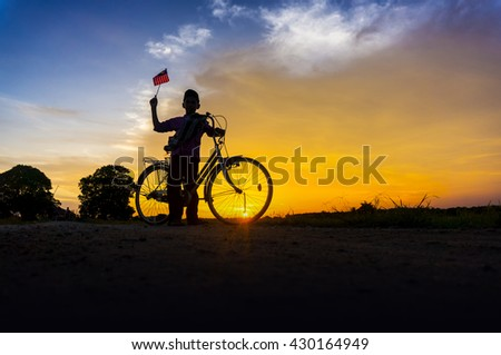 silhouette boy holding the malaysia flag during dramatic sunset - stock photo